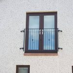 Simple metal balcony railing with basket design to compliment the property's brown patio doors in Irvine, Ayrshire.