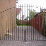 These tall wrought iron driveway gates with simple design are finished in a black paint on the railings and gold paint on the spearheads and bushes to make them stand out. Designed and fitted in Kilmarnock, Ayrshire.