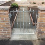A galvanised silver metal gate with alternating spearheads and decorative bushes. Low maintenance and no rust, fitted to last in Troon, Ayrshire.