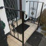Elegant black scroll design metal handrail fitted at the customer's front door steps in Irvine, Ayrshire.