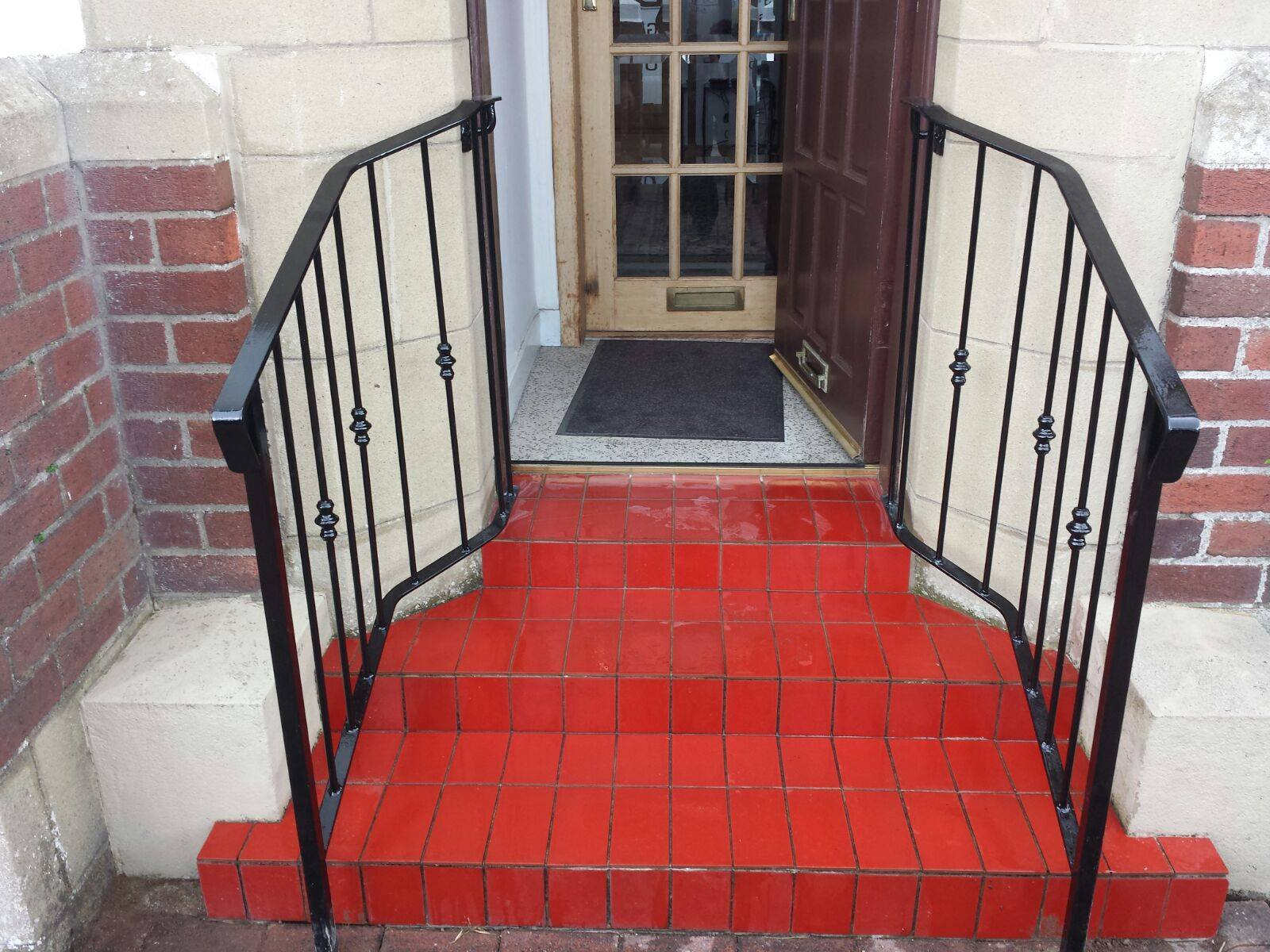 Matching handrails with decorative metal bushes, finished in black gloss. Handrails installed in Troon, Ayrshire by Dain Art Iron