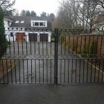 Classy black metal double driveway gates with circle design and sphere railheads. Designed and fitted in Irvine, Ayrshire.