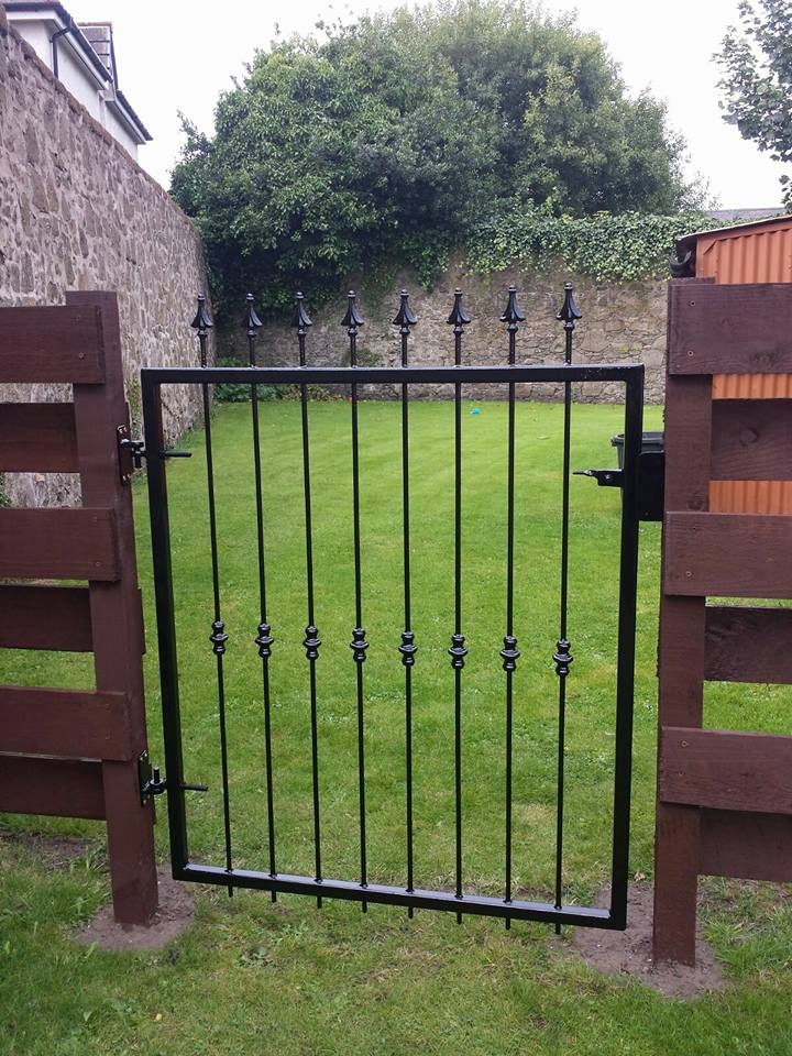A box section black metal gate with spearheads and bushes. Made to measure to fit customer's existing wooden fencing in Kilmarnock, Ayrshire.