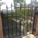 A custom designed, black metal single gate built and fitted by Dain Art Iron in Ayrshire. The curved design, finished with spearheads and diamond motif in the centre really make this gate stand out.
