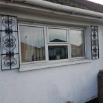 Decorative iron black window shutters with scroll design in Irvine, Ayrshire.