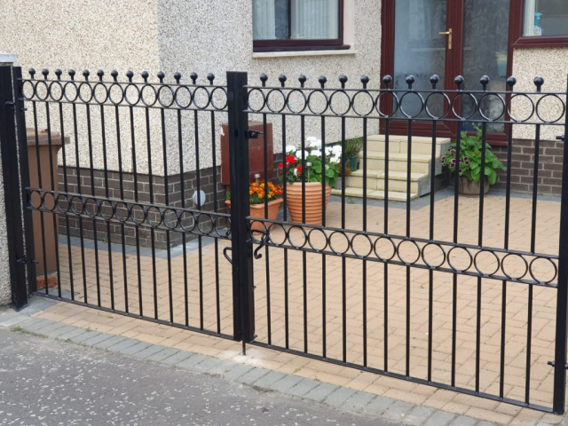 Straight top driveway gates with circles and spheres.